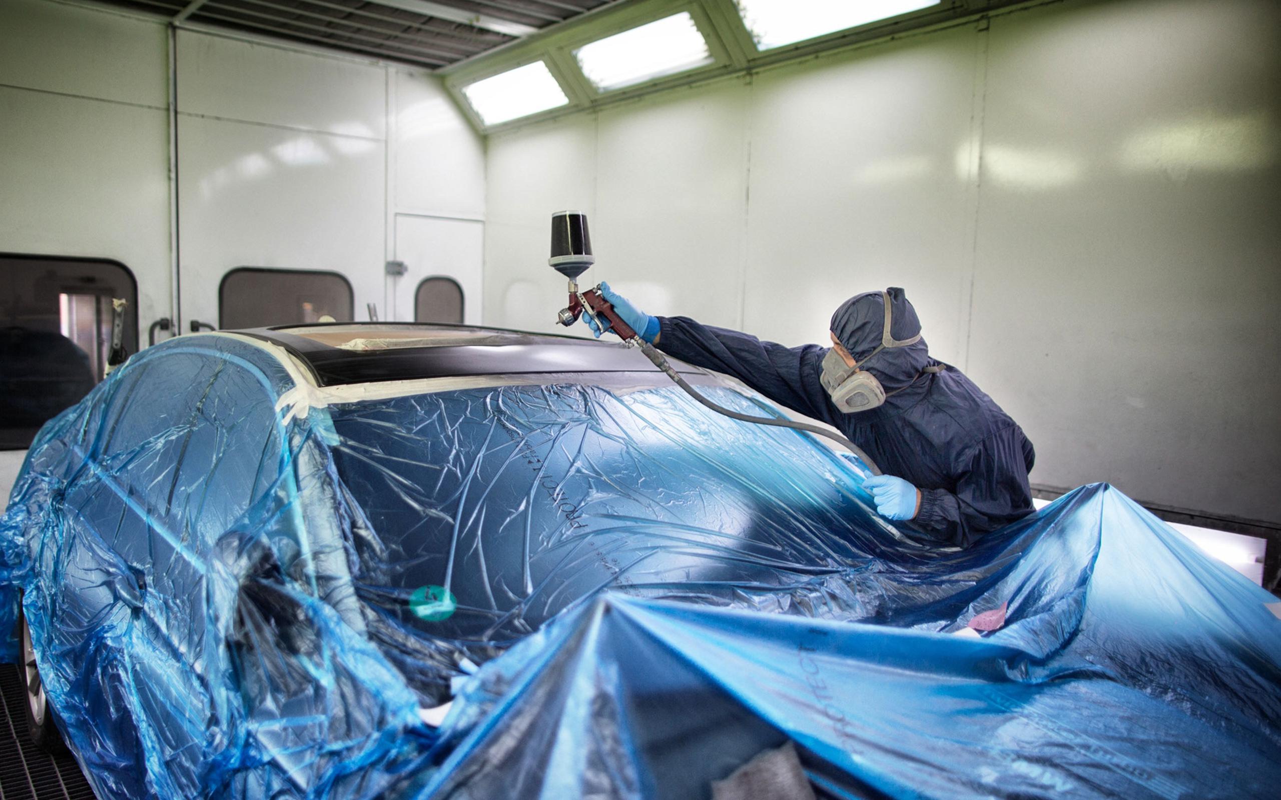 Mitarbeiter in Schutzkleidung lackiert ein Auto - Karosseriebau und Lackiererei Kolahi e.k. seit 1997 in Mönchengladbach